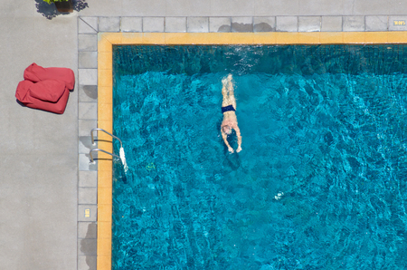 Man swim in the pool at the hotel. View from above. Stock Photo