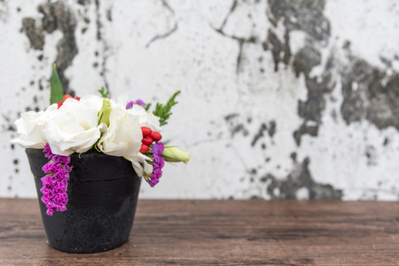 Colorful flowers are made up of white Lisianthus flowers and purple statice in black pots, with old concrete floors as backgrounds. represents the freshness of spring.