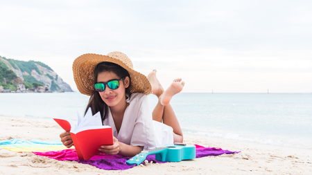 Asian women in white suit wearing wide hats and sunglasses, resting in the sun on the beach on a vacation. Happily smiling Reklamní fotografie