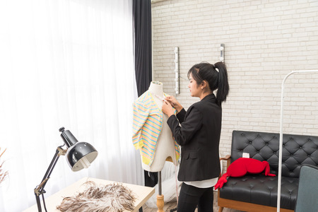 Smiling Young Asian designer tailor a dress working on her designs in the studio near mannequin in office. Fashion designer stylish showroom concept. fashion design using digital tablet Reklamní fotografie