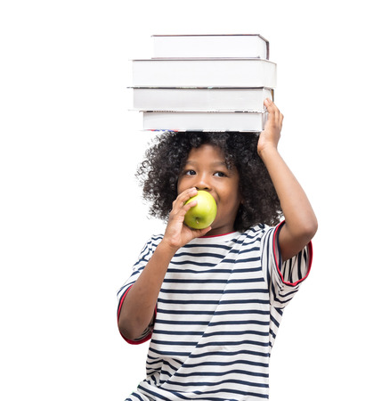 Black boy are holding his school books and a green apple. Little black Children with apple on the book on his head, education concept back to school Stock Photo