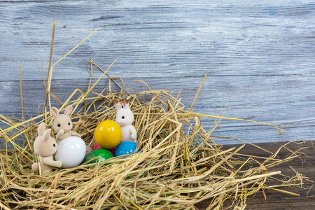 Many rabbit dolls are with multiple eggs in the straw stack. Reklamní fotografie