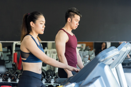 Side view of Attractive young muscular man and women are smiling while running on the treadmill machine. a treadmill in gym. Cardio training. Reklamní fotografie