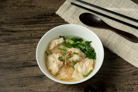 Shrimp wonton with braised pork in soup on wooden table - Asian food style   Select focus image Reklamní fotografie