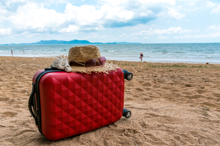 Red luggage and hat on the beach with blue sky, Traveling on a summer vacation on a cloudy day. Suitable for relaxation.