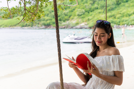 Asian girl in white dress smiling happily by the sea for summer, Traveling on vacation. Read books on the beach swings on summer vacation.