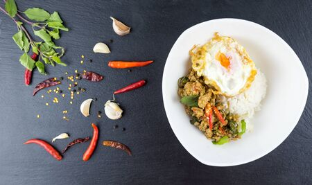 Spicy Thai basil with Crispy Chicken and Egg (Pad Krapow Gai) on table