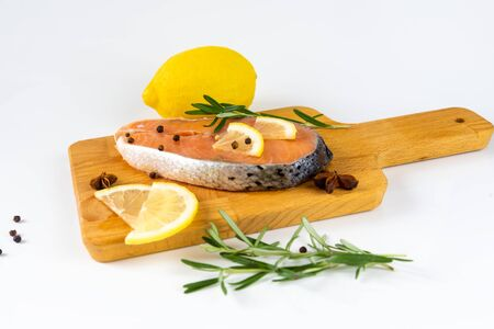 Grilled salmon steak on vintage wooden board with fork, olive oil, vegetables, herbs and spices on dark concrete background. Raw salmon fillet with vegetables, spices and lemon on wooden table. Zdjęcie Seryjne