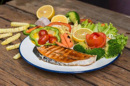 Salmon fillets. Grilled salmon, salmon steak on old wooden table, vintage style