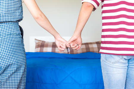 Men and women stand hand in front of the bed on Valentine's Day. Close up back of couple in love holding hands with couch Stockfoto