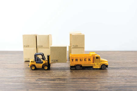 Concept logistic of warehouse, Worker driver a forklift loader between rows in the big warehouse is loading cardboard boxes on pallet to shelves Stockfoto