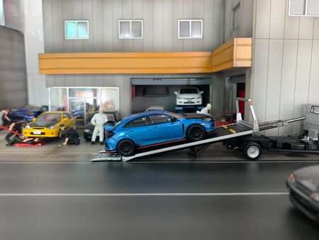 selective focus of miniature Blue cars are being loaded into trucks transported by trucks from the garage. miniature Car mechanic is in the process of repairing the car in the spare parts shop.