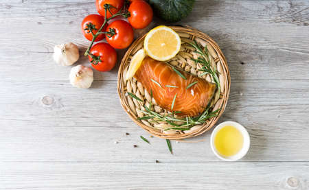 Grilled salmon steak on vintage wooden board with fork, olive oil, vegetables, herbs and spices on dark concrete background. Raw salmon fillet with vegetables, spices and lemon on wooden table. Stockfoto