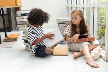 the happiness caucasian girl kid and black boy smile have fun are sitting and reading books, with books all around for prepare to go to school