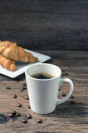coffee break, White coffee cup, croissants on wood table background, selective focus. Breakfast concept