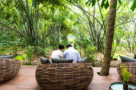 A couple of men and women sit on wicker chairs in the garden with a soothing natural atmosphere. Stockfoto