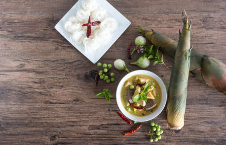 Chicken green curry with bamboo shoots and blood pudding (Kaeng kheiyw hwan) on dark wooden background with Thai tradition food served with steamed rice. Thai food very popular Stockfoto