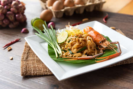 Pad Thai with fresh shrimp on a wooden table Pad Thai is a delicious Thai street food. And popular people around the world