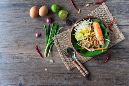 Pad Thai with fresh shrimp on a wooden table Pad Thai is a delicious Thai street food.