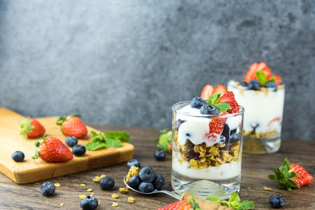 Bowl of homemade granola with Greek yogurt and fresh berries mix on wooden background from top view. Healthy blueberry and Strawberry parfait in a jar. Stockfoto