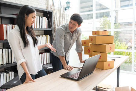 professional young online shopping company team of two co worker with box of products in office background and face to camera. selective focus photo. Stockfoto