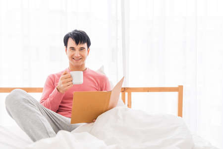 The young man was awakened by the morning alarm clock while on the bed.Shallow depth of field.unhappy from noisy sound of alarm clock and trying to turn it off. Hangover,lazy and sleepless concept. Stockfoto