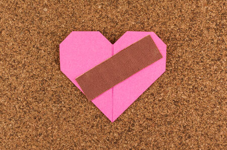 Heart with plaster on corkboard background photo