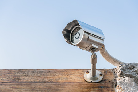 CCTV camera on wooden wall against sky photo