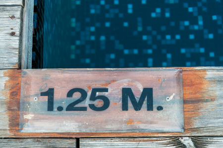 1.25 m. depth marking on pool edge photo