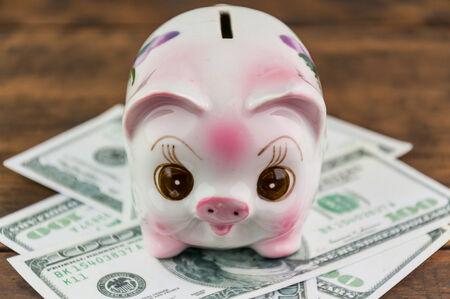 banco dinero: Hucha y dinero en el fondo de madera