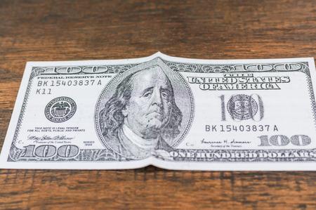 Sad Franklin dollar bill on wood background: concept for\ debt