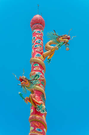 Chinese colorful dragon on pole against blue sky background photo