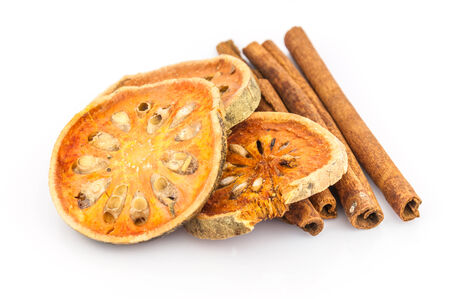 dry bael with cinnamon isolated on white background, healthy food photo