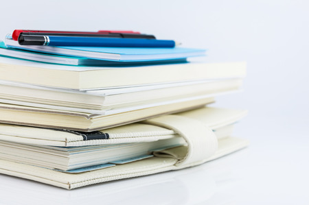 stack of organizer, notebooks, pen and pencil on white background photo