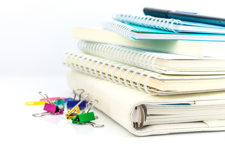 stack of organizer, notebooks, pen and colorful paper clips on white background photo