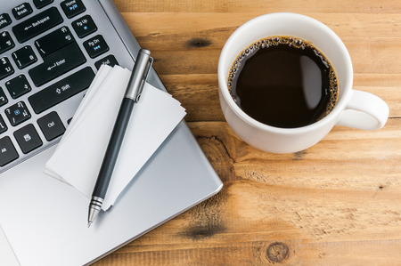 business card and pen over laptop with coffee cup on wooden table photo