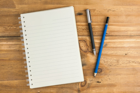 blank notebook with pen and pencil on wooden table, business concept photo