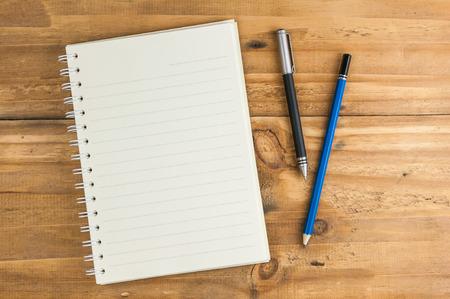prázdné notebook s perem a tužkou na dřevěném stole, obchodní koncept
