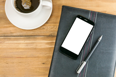 notebook with blank screen smart phone, pen and coffee cup on wooden background, mobile business concept photo