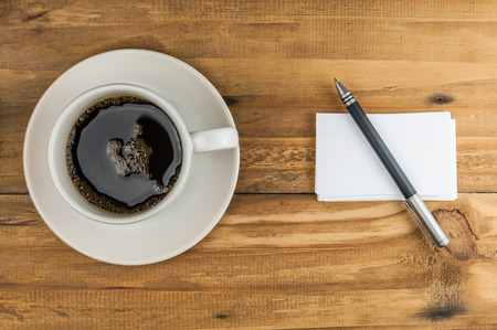 business card with pen and coffee cup on wooden table photo