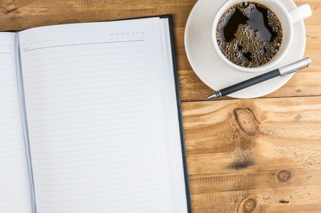 notebook with pen and coffee cup on wooden background, business concept