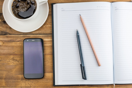 notebook with pen, pencil, smart phone and coffee cup on wooden background  photo