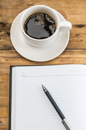 notebook with pen and coffee cup on wooden background  photo