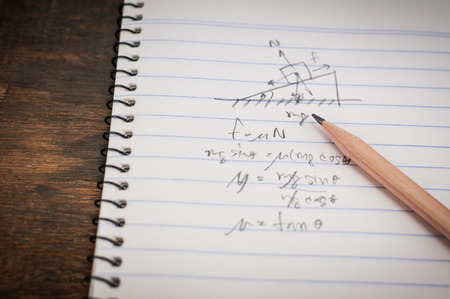 Physics calculation on notebook with pencil photo