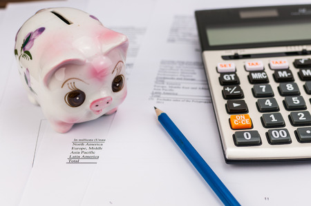 piggy bank with calculator and pencil on document background photo
