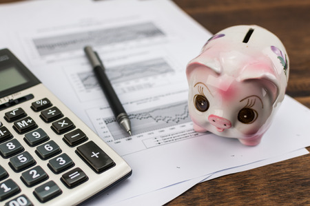 piggy bank with calculator and pen on document background photo