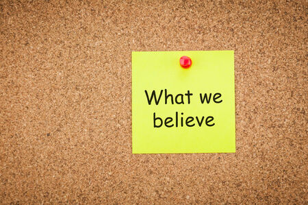 sticky note with word what we believe on corkboard, business concept