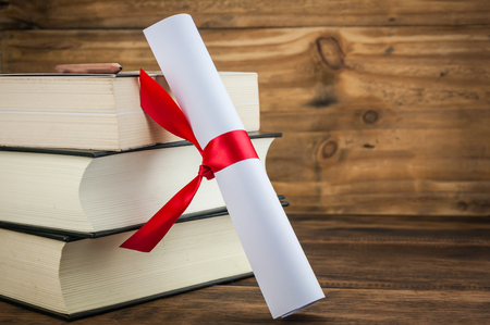 A Parchment Diploma Scroll Rolled Up With Red Ribbon Beside Stack Of Books On