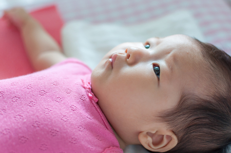 Asian 3 months baby girl looking at mobile. Banco de Imagens
