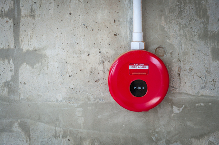 Fire alarm switch on concrete wall background. Banco de Imagens
